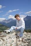 Lächelnder Jugendlicher, der auf einer Wand sitzt Stockfotos
