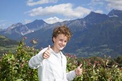 Lächelnder Jugendlicher, der oben Daumen aufwirft Lizenzfreies Stockfoto
