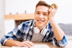 Lächelnder Jugendlicher, der am Tisch mit einem Apfel sitzt Stockfotos