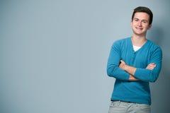 Lächelnder Jugendlicher mit den gekreuzten Armen Stockfotografie