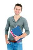 Lächelnder Jugendlicher mit Lehrbüchern und der Hand in der Tasche stockbild