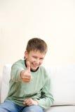 Lächelnder Jugendlicherscheinendaumen herauf Zeichen Lizenzfreies Stockfoto