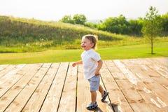 Lächelnder Junge auf dem Gebiet am sonnigen Sommermorgen Junge im weißen Hemd Die Familie reist, Kind lief glücklich um stockbild