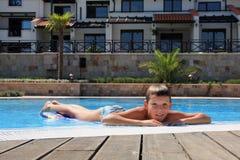 Lächelnder Junge auf dem Rand des Swimmingpools Stockfotografie