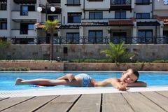 Lächelnder Junge auf dem Rand des Swimmingpools Lizenzfreie Stockfotografie