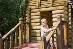 Lächelnder Junge auf der Eingangsterrasse des Hauses Stockfotografie