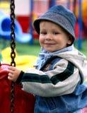 Lächelnder Junge auf einem Merry-go-round Stockbilder