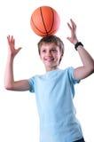 Lächelnder Junge, Basketball-Spieler, der Spaß mit einem Ball hat stockfoto
