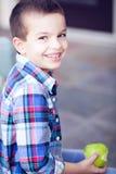 Lächelnder Junge, der Apfel isst Stockfoto