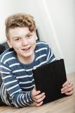 Lächelnder Junge, der auf Boden mit Tablet-Computer liegt Stockbild