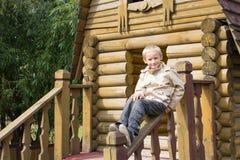 Lächelnder Junge, der auf dem Geländer des Hauses sitzt Stockbild