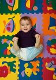 Lächelnder Junge, der auf dem Puzzlespiel liegt Stockfotos