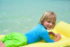 Lächelnder Junge, der auf dem Strand mit Luftmatraze spielt Lizenzfreie Stockbilder