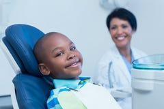 Lächelnder Junge, der auf eine zahnmedizinische Prüfung wartet Stockbild