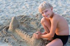 Lächelnder Junge, der auf sandigem b spielt Lizenzfreies Stockfoto