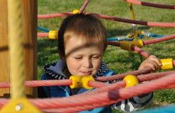 Lächelnder Junge, der auf Spielplatz spielt Stockbild