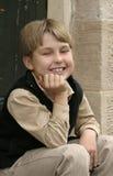 Lächelnder Junge, der auf Türstufe sitzt stockbilder