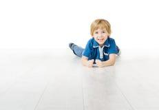 Lächelnder Junge, der auf weißem Boden liegt Lizenzfreies Stockfoto