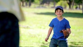 Lächelnder Junge, der Baseball bei der Stellung aufrecht spielt stock footage