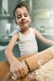 Lächelnder Junge, der den Teig knetet Stockbilder