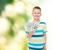 Lächelnder Junge, der Dollarbargeld in seiner Hand hält Stockbilder
