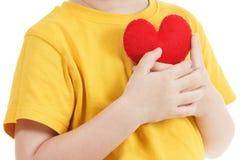 Lächelnder Junge, der eine rote Herzfigürchen hält Symbol der Liebe, Familie, Konzept der Familie und der Kinder Lizenzfreie Stockfotos