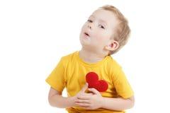 Lächelnder Junge, der eine rote Herzfigürchen hält Symbol der Liebe, Familie, Konzept der Familie und der Kinder Lizenzfreies Stockfoto
