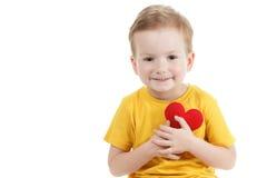 Lächelnder Junge, der eine rote Herzfigürchen hält Symbol der Liebe, Familie, Konzept der Familie und der Kinder Lizenzfreies Stockbild