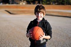 Lächelnder Junge, der einen Basketball auf einem Spielplatz hält Stockfotografie