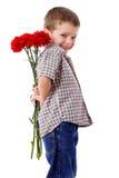 Lächelnder Junge, der einen Blumenstrauß versteckt Lizenzfreies Stockfoto