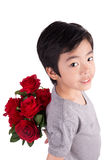 Lächelnder Junge, der einen Blumenstrauß von roten Rosen hinter, isolat versteckt Stockfotos