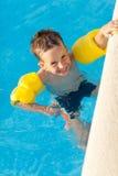Lächelnder Junge, der einen Spaß am Swimmingpool hat lizenzfreie stockbilder