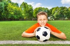 Lächelnder Junge, der Fußball mit beiden Armen hält Lizenzfreie Stockfotografie