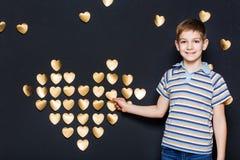 Lächelnder Junge, der goldenes Herz zusammenbaut Lizenzfreie Stockbilder