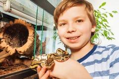 Lächelnder Junge, der königliche Pythonschlange in seinen Händen hält stockbilder