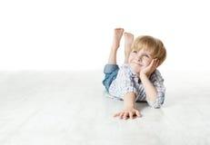 Lächelnder Junge, der sich auf Fußboden hinlegt und oben schaut Stockfoto