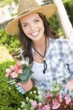 Lächelnder junge Frauen-tragender Hut, der draußen im Garten arbeitet Stockbilder