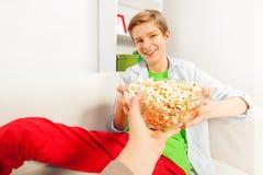 Lächelnder Junge hält Popcornschüssel von jemand Hand Stockbild