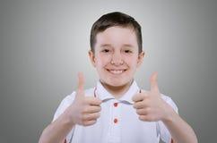Lächelnder Junge hält seinen Daumen hoch Lizenzfreie Stockfotos