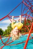 Lächelnder Junge hängt umgedrehtes auf Seil des roten Netzes Stockfotos