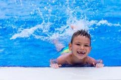 Lächelnder Junge haben Spaßspritzwasser in schwimmendem poo stockbild