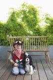 Lächelnder Junge im Cowboy Costume With Dog auf Plattform Stockbild
