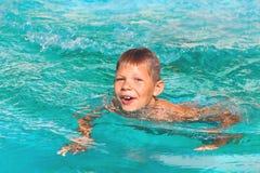 Lächelnder Junge im Swimmingpool stockbild