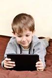 Lächelnder Junge ist, spielend liegend und auf einer Tablette Stockfotografie