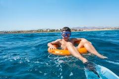 Lächelnder Junge lernt, auf Rettungsring im Meer zu schwimmen Lizenzfreies Stockfoto