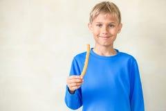 Lächelnder Junge mit berühmten spanischen Nachtisch churros lizenzfreie stockbilder