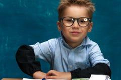 Lächelnder Junge mit Brillen auf blauem Hintergrund Stockbild