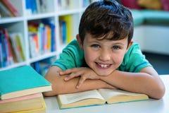 Lächelnder Junge mit Buch in der Schulbibliothek Stockfotografie