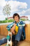 Lächelnder Junge mit dem Skateboard, das allein sitzt Stockfotografie