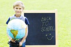 Lächelnder Junge mit einer Kugel gegen die Tafel Bildung zurück zu Schulkonzept Stockfotografie